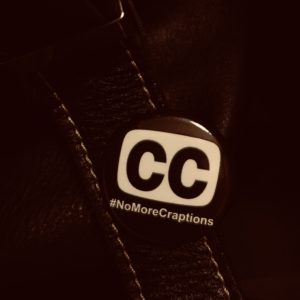 Close-up of CC #NoMoreCraptions button. CC logo in black and white on button, pinned to black leather bag. VWells image of Rikki Poynter button.