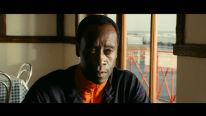 A reaction shot still from The Guard, a 2011 crime comedy film starring actors Don Cheadle and Brendan Gleeson. Directed by John Michael McDonagh.