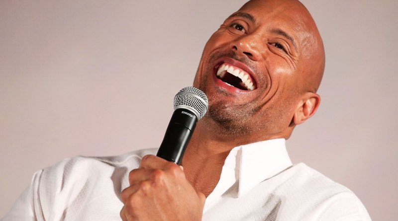 "photo of actor and entertainer, dwayne ""the rock"" johnson laughing while wearing a white shirt and holding a microphone."