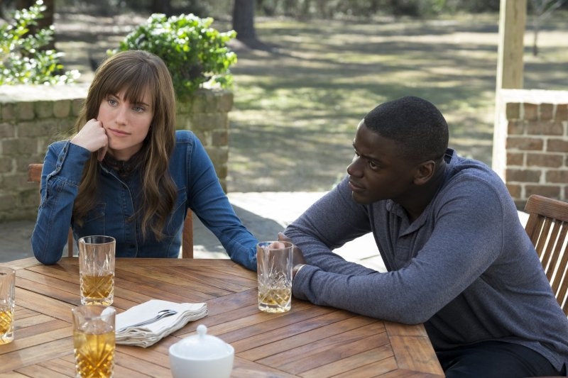 An image of Allison Williams and Daniel Kuluuya sitting and holding hands in the 2017 horror movie, Get Out.
