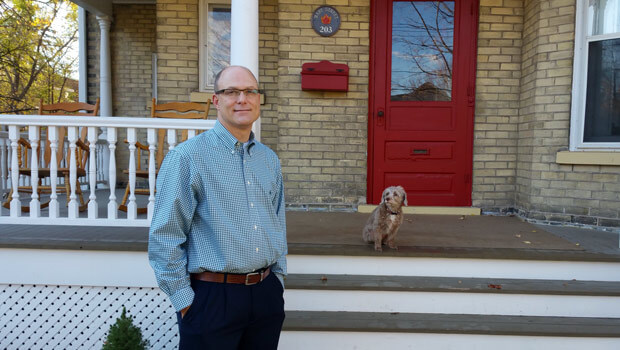 Jeffrey Casello and pooch in front of their century home