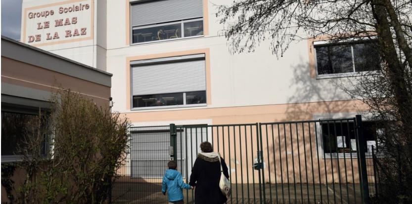 Devant l'entrée du groupe scolaire Le Mas de la Raz, à Villefontaine (Isère), mardi 24 mars 2015. (PHILIPPE DESMAZES / AFP)