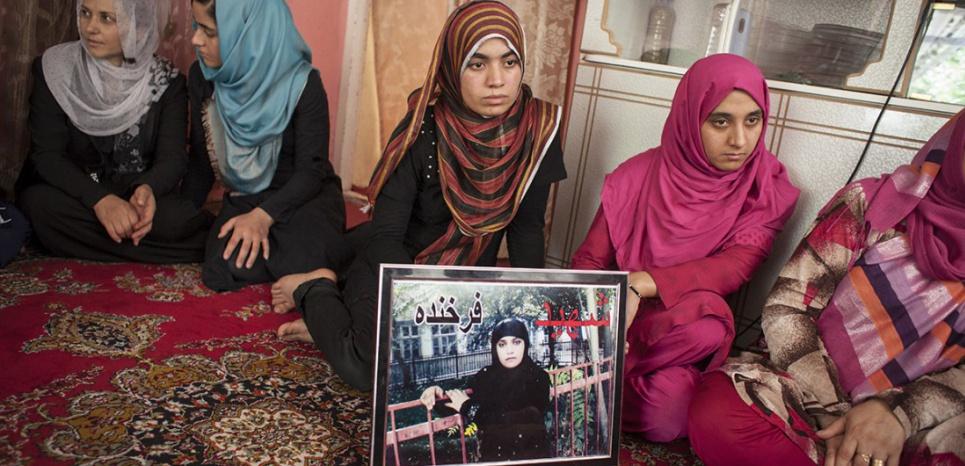Les sœurs de Farkhunda derrière son portrait dans le salon familial. (Sandra Calligaro/PictureTank pour L'Obs)