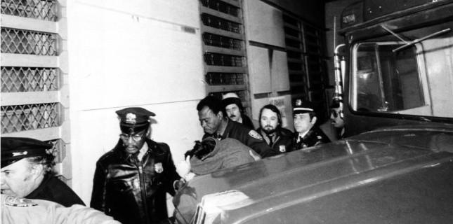 Mark David Chapman entre les mains de la police et des médecins, après le meurtre de John Lennon, le 8 décembre 1980. (AP/SIPA)