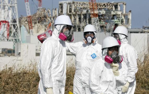 Journalistes escortés par des employés de Tepco, portant des combinaisons et des masques de protection, regardent les bâtiments réacteurs 3 et 4 de la centrale nucléaire de Fukushima Daiichi, Okuma, préfecture de Fukushima, le 28 février 2012 (M.KIMIMASA/