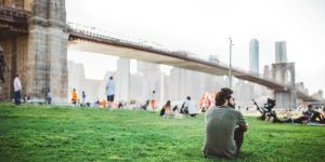 Man die zit op het gras met uitzicht over New York