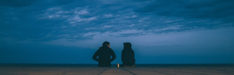 Silhouette of two people sitting on the ground with a clouded dark sky overhead