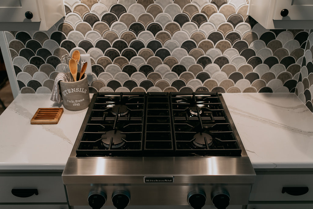 Stovetop in grey contemporary kitchen with grey, black, and brown backsplash