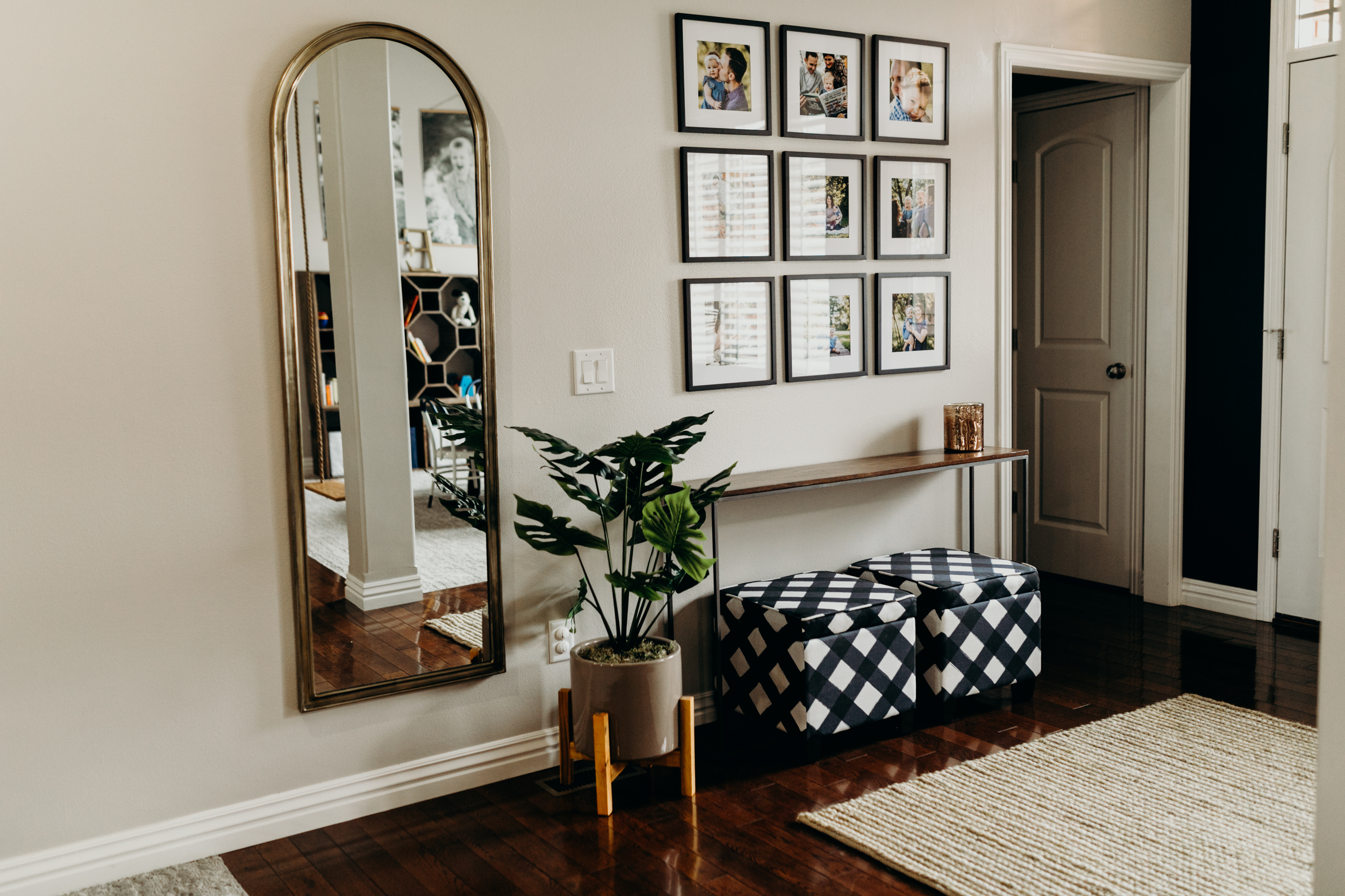 Entry way with mirror, picture frames, and small table
