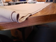 A piece of fabric stretches out on Amy's work table. Amy will use the rest to make the bottom cover and sleeves of the dress.