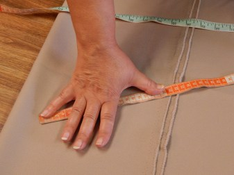 """Amy measures a sleeve she is preparing. """"My mother and grandmother taught me to use my hands to measure."""""""