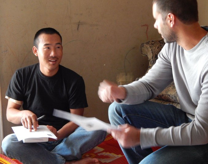 Po Khu receives help from his friend Caleb Benningfield in Po Khu's apartment Nov. 1, 2013. Po Khu learns English and the Bible from his friends regularly.