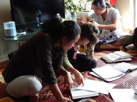 Ka Tay, a refugee from Myanmar, quietly works on a bible study worksheet with her friend. Ka Tay wants to get her driver's license someday so she can be independent and help her community. Getting to English classes is difficult without a car.
