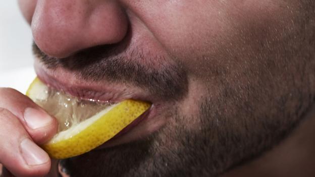 Alguien comiendo una rodaja de limón