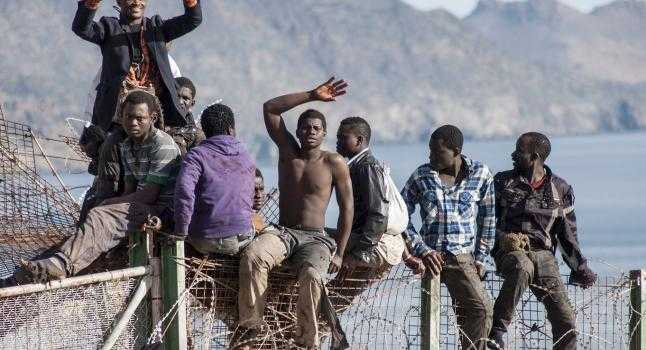 Un grupo de personas se trepa a la valla que separa las fronteras entre Marruecos y el territorio español de Melilla, el 3 de abril de 2014, en un intento por migrar a España. (BLASCO DE AVELLANEDA/AFP/Getty Images)
