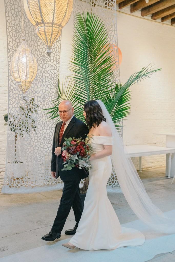 Bride in wedding dress walking down the aisle at Regency Event Venue