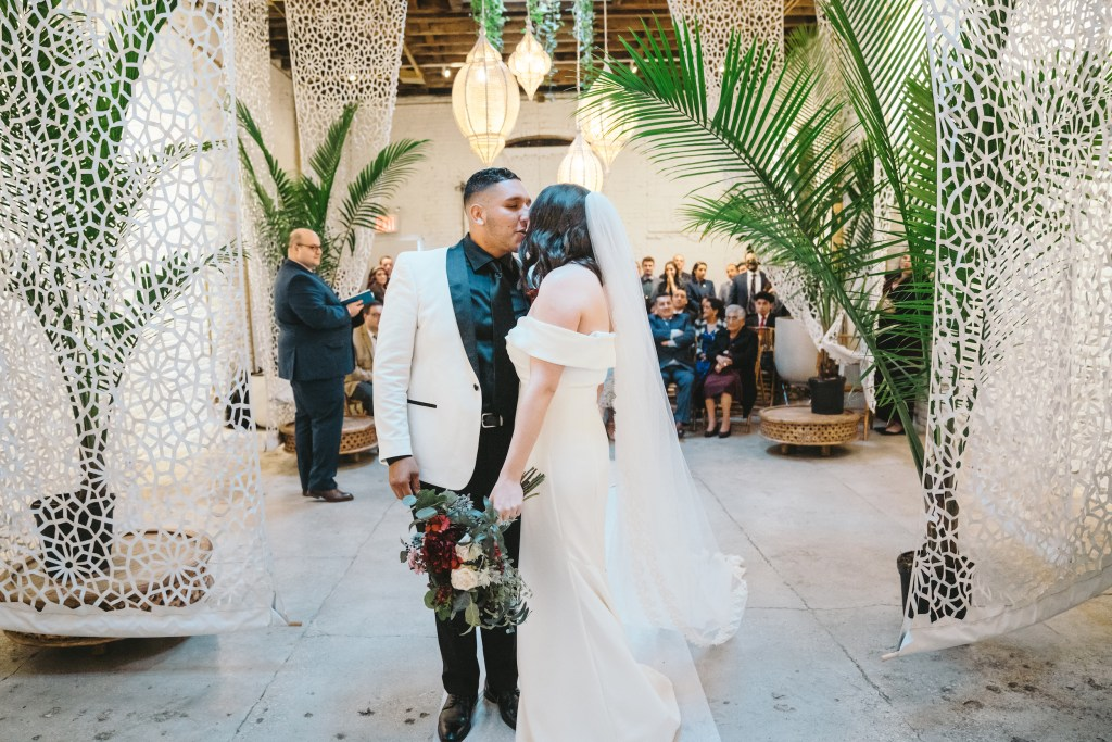 Bride and groom kiss with audience behind at the White Room of Regency Event Venue
