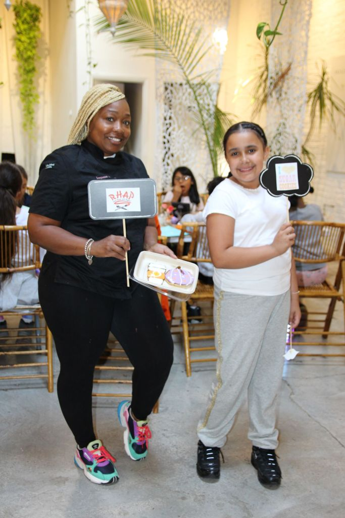Woman in black stands holding a sign with a child at an educational workshop on custom desserts by A Cake Baked in Brooklyn