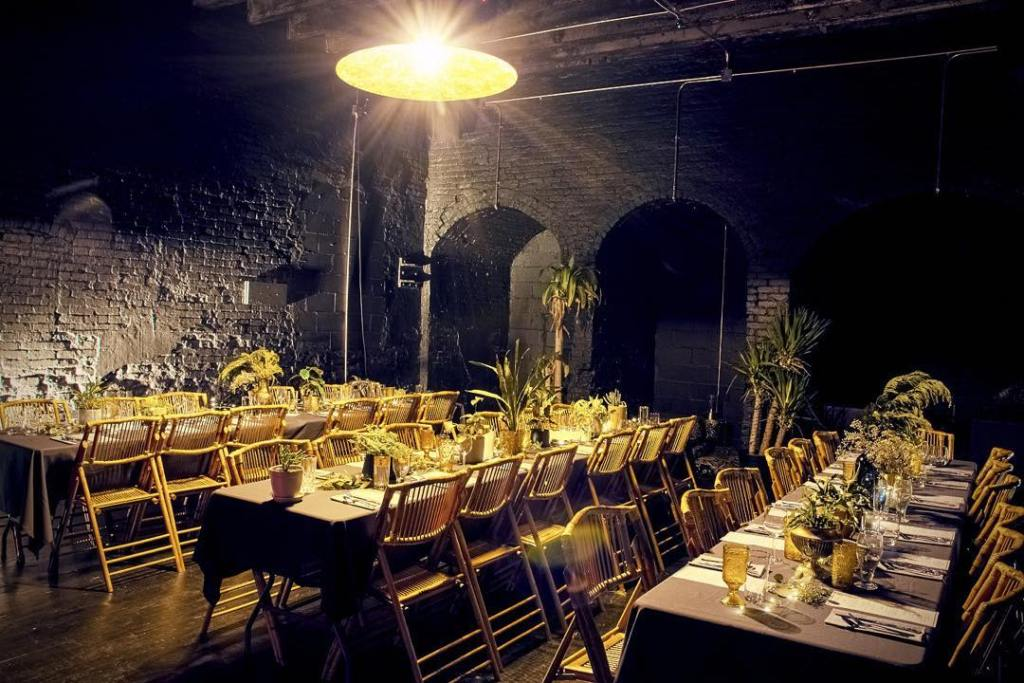 Dining Tables set with plants an silverware at Regency Black Room in Brooklyn, New York.