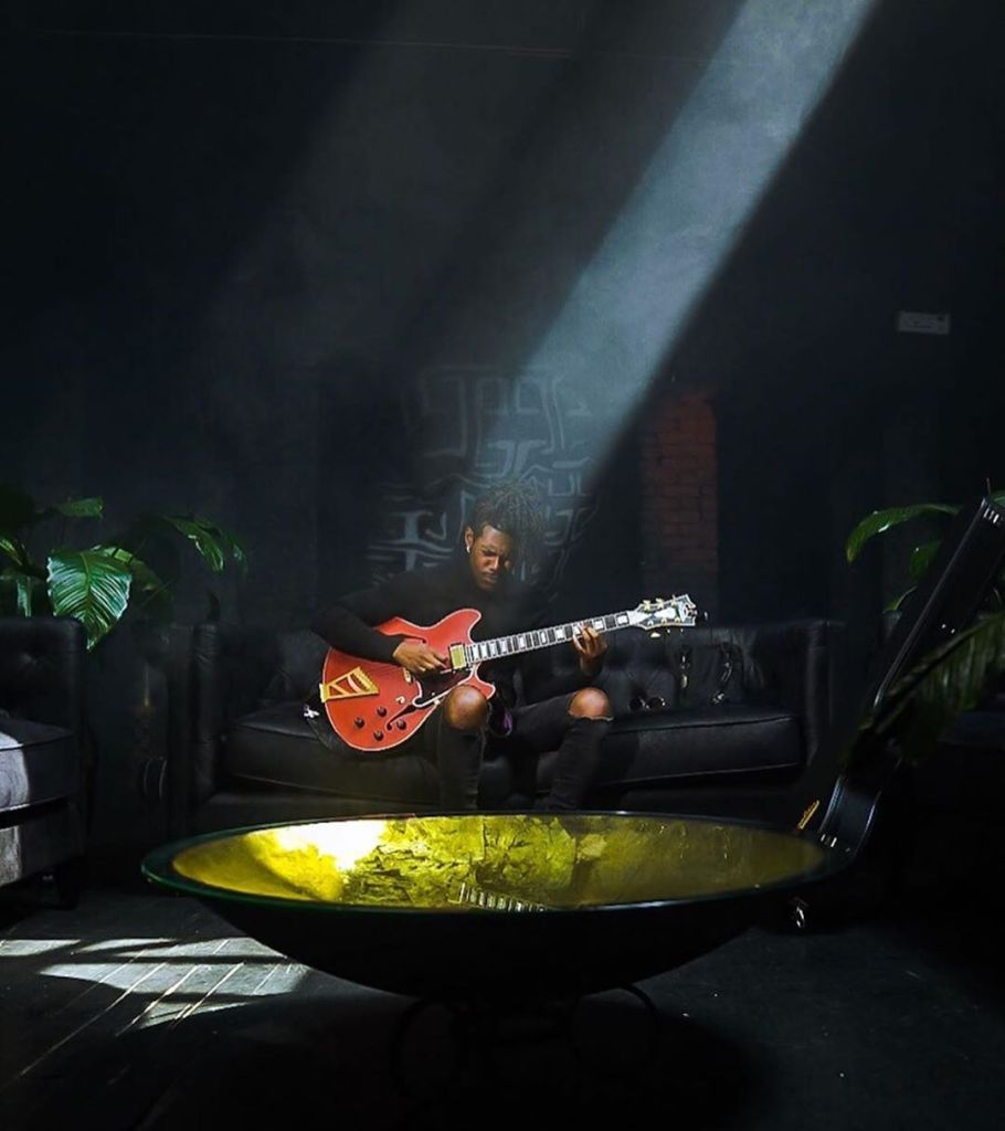 Man plays guitar with shaft of light piercing the darkness in the black room of Regency