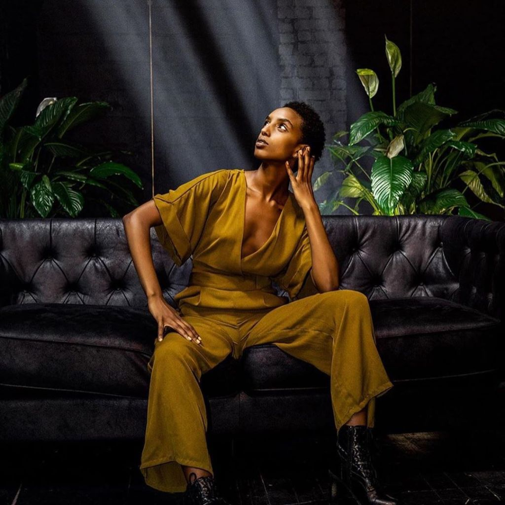 Model on couch illuminated in the black room of Regency Event Venue in Brooklyn, New York