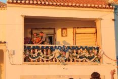 Locals decking out their balcony with flowers in preparation for a festival on that evening