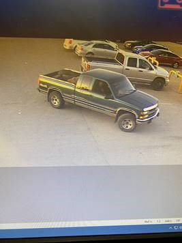 The suspect vehicle is described as a green GMC Sierra or Chevrolet Silverado truck with no license plate.