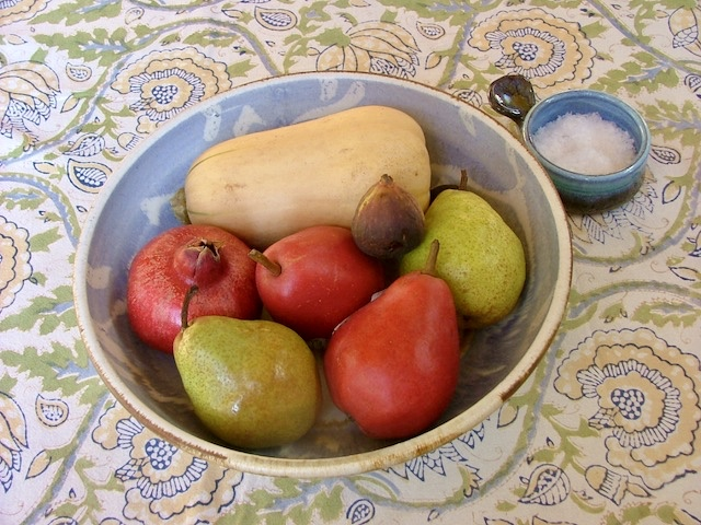 Winter squash, pears, pomegranite and a fig, in ceramic bowl. On tablecloth-covered table with a small bowl of sea salt.