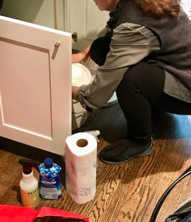 Woman pulling out a can of laundry soap. On a wood floor is a roll of paper towels, Mrs. Myers spray, and Jet-Dry Rinse Agent.