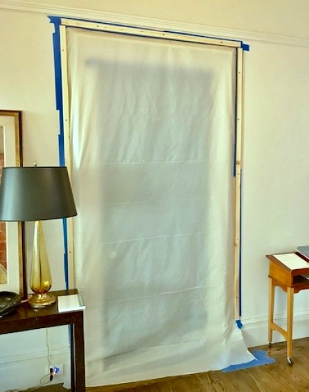 Plastic sheeting taped over doorway. Tables on either side of door, one with lamp.