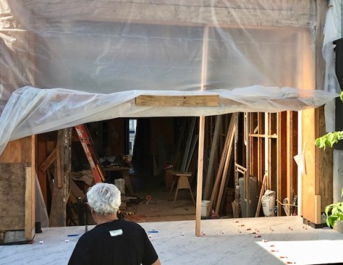 Contractor facing gutted downstairs room, from outside.