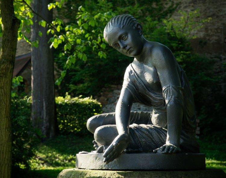 Eisenkunstgussfigur im Schlosspark von Wolkenburg, Knöchelspielendes Mädchen