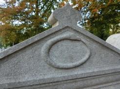 Het symbool van een slang die zijn eigen staart bijt, ook wel de Ourobos genoemd. Dit is een eeuwigheidssymbool. Maar één graf op de begraafplaats heeft dit symbool.