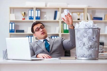 Man in office flippantly throws balls of paper in bin