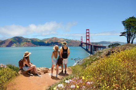 Three people looking at the Golden Gate Bridge, San Francisco, California
