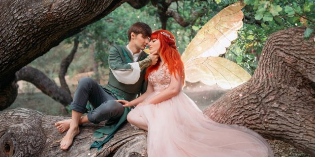 A young man and a sprite with wings about to kiss in a tender moment in the woods