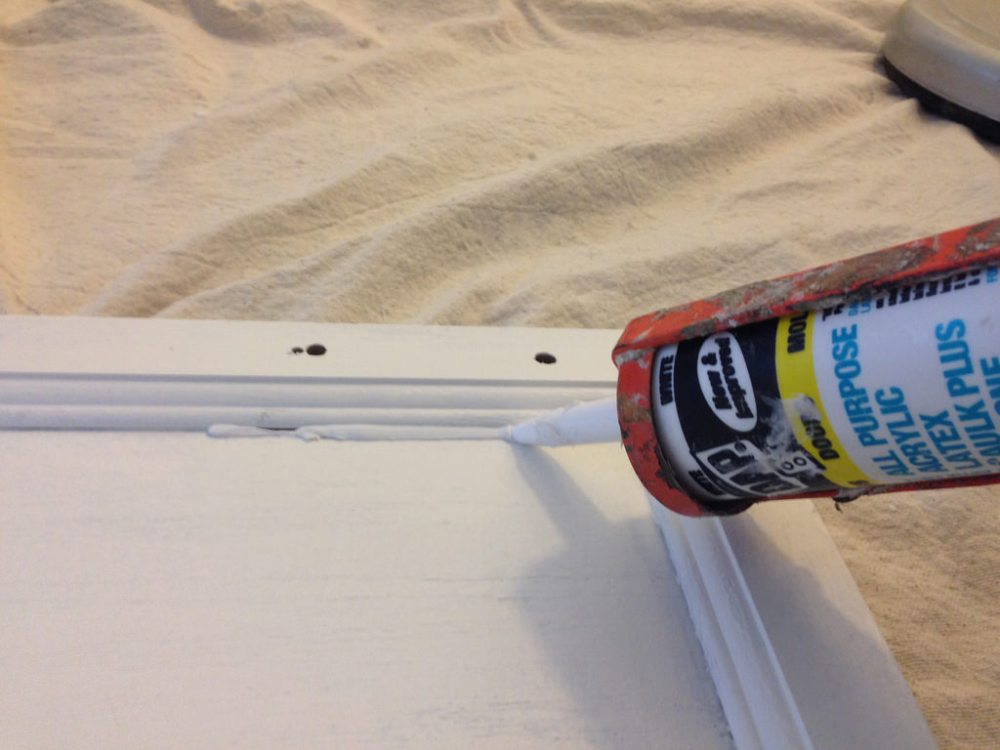 Caulking cabinet doors before painting.