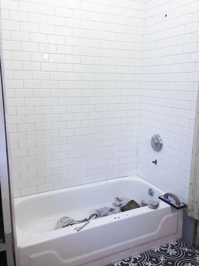 Installation of a subway tile tub surround.