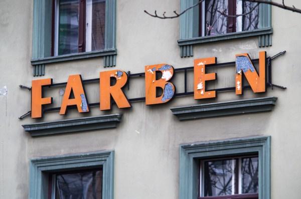 """Hauswand mit Schriftzug """"Farben"""", dessen Farben abblättern."""