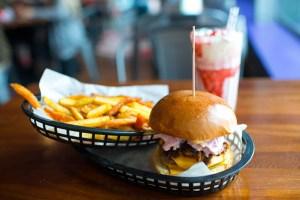 De er berømte burgerne fra Almost Famous. Her en Triple Nomnom med pommes frites av vanlige poteter og søtpoteter, samt en heftig jordbærmilkshake.