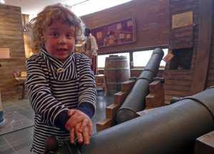 Kind an einer Spielzeugkanone.