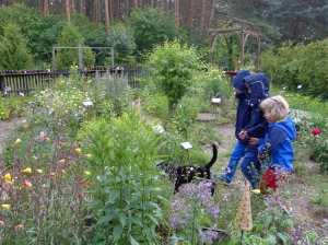 Kleinkinder laufen hinter einer schwarzen katze im Kräutergartn von Ina Schirner auf Usedom hinterhe, Familienurlaub Usedom, Tipps Familienreise, Aktivurlaub mit der Familie, Usedom-Urlaub, Reiseblog. Reisefeder