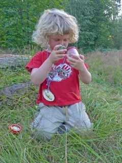 Blondes Kleinkind, das ein Insekt in seiner Becherlupe beobachtet