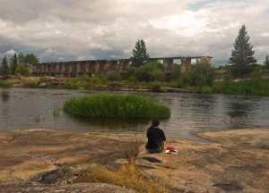 Frau sitzt auf einem Felsen vor den Ruinen vom Wasserkraftwerk