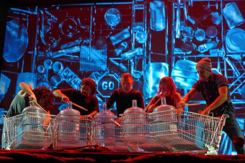 Akteure von Stomp machen Musik mit leeren Wasserflaschen