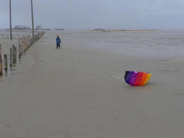 Kind mit Drachen am Strand