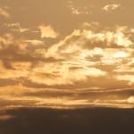 Güldene Wolken über dunkler Nordseeinsel bei Sonnenaufgang