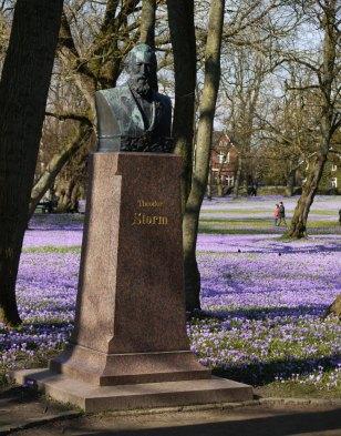 Theodor Storm blickt von seinem Sockel im Park direkt auf die Krokus-Pracht