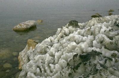 Salzkrusten ziehen sich ich auch über Felsen im Wasser