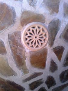 Rejilla redonda instalada sobre una superficie de pizarra y cemento.